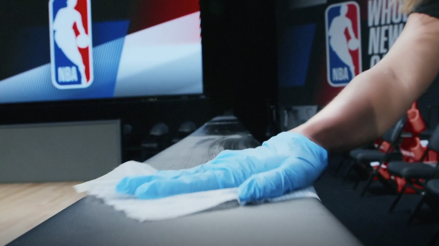 a person at an nba game wiping down a surface with a clorox wipe while wearing a blue glove