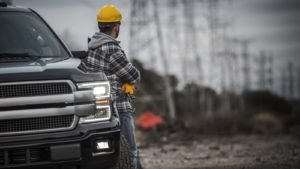 A worker rests on a pickup truck with high-voltage poles in the background.