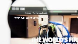 Image of Arcimoto's (FUV) logo amplified by a magnifying glass on the company's home web page.