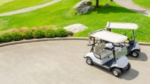 Two golf cars are parked on the green course.
