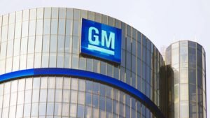 Image of General Motors (GM) logo on corporate building with clear sky in the background