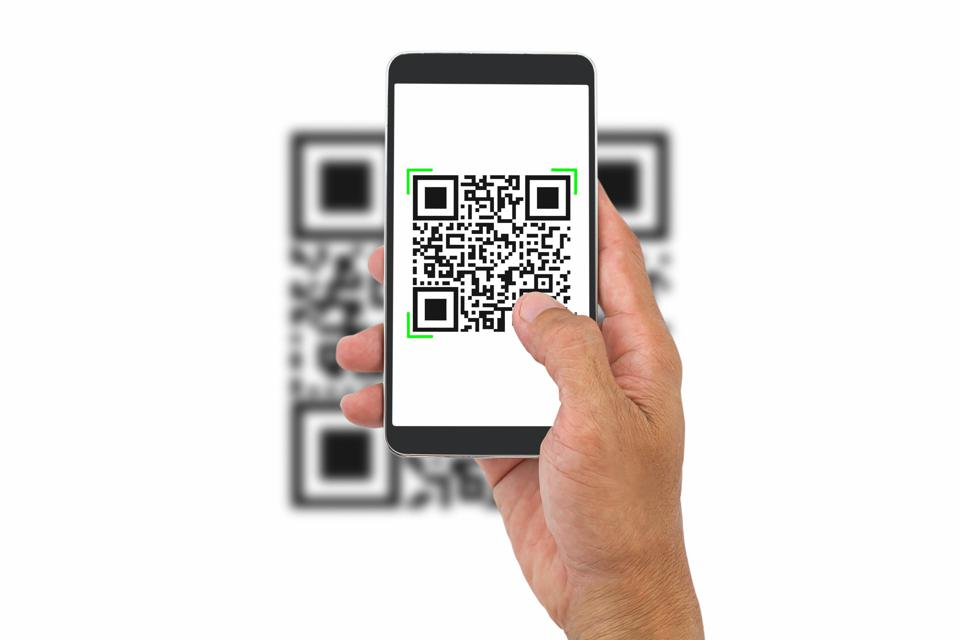 Hand holding smartphone scanning QR code on white background, business concept