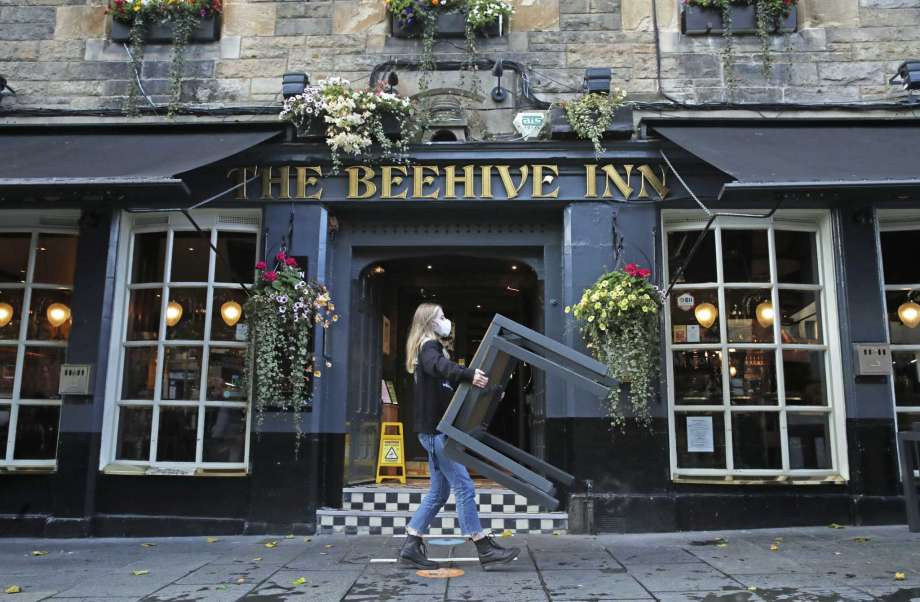 A worker removes tables from outside the Beehive Inn, as temporary restrictions announced by First Minister Nicola Sturgeon to help curb the spread of coronavirus have come into effect from 6pm, in Edinburgh, Friday, Oct. 9, 2020. (Andrew Milligan/PA via AP) Photo: Andrew Milligan, AP / PA