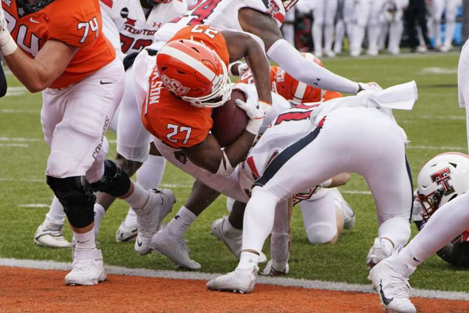 Oklahoma State running back Dezmon Jackson (27) scores against Texas Tech in the first half of an NCAA college football game in Stillwater, Okla., Saturday, Nov. 28, 2020. Photo: Sue Ogrocki, AP / Copyright 2020 The Associated Press. All rights reserved.