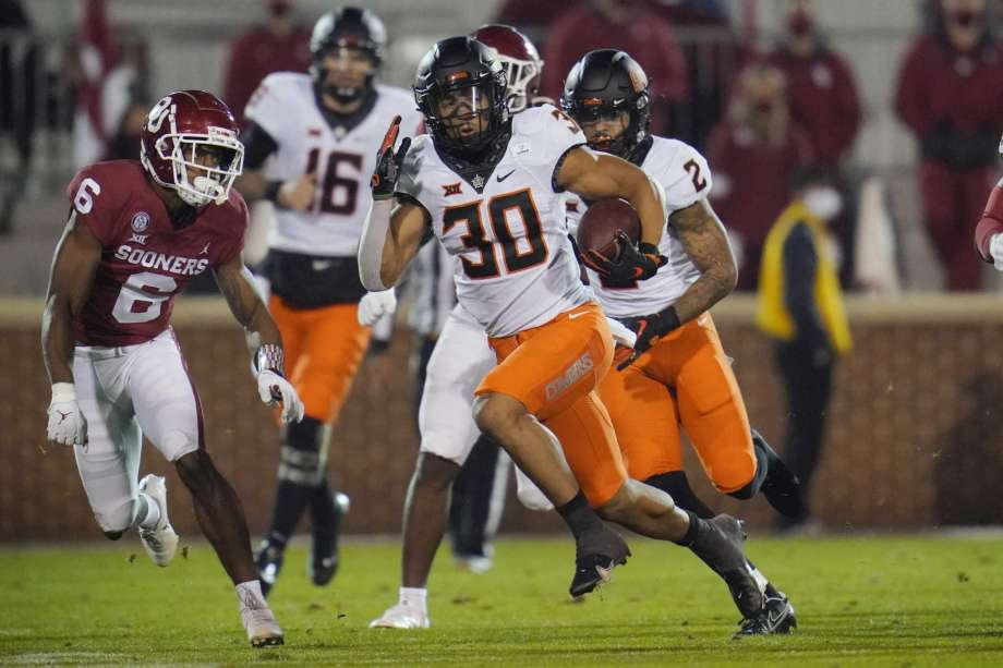 Oklahoma State running back Chuba Hubbard (30) carries past Oklahoma cornerback Tre Brown (6) during the first half of an NCAA college football game in Norman, Okla., Saturday, Nov. 21, 2020. Photo: Sue Ogrocki, AP / Copyright 2020 The Associated Press. All rights reserved.