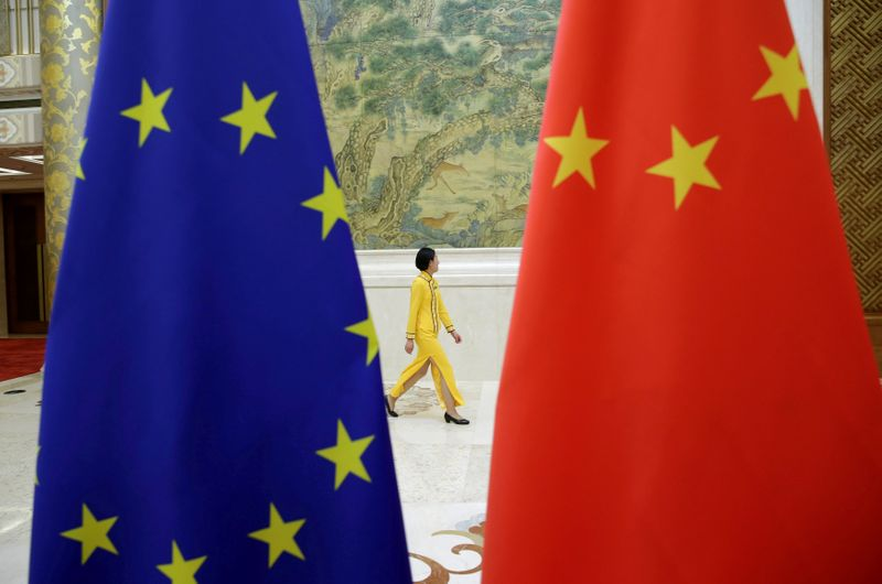 © Reuters. FILE PHOTO: An attendant walks past EU and China flags ahead of the EU-China High-level Economic Dialogue in Beijing