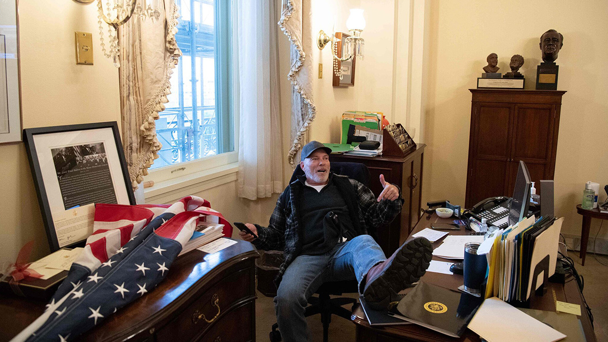 A Trump supporter sits at Speaker Nancy Pelosi's desk after rioters stormed the Capitol Building
