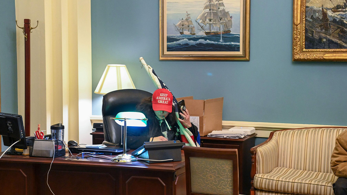 A woman wearing a MAGA hat sits in a government office after Trump supporters raided the Capitol Building