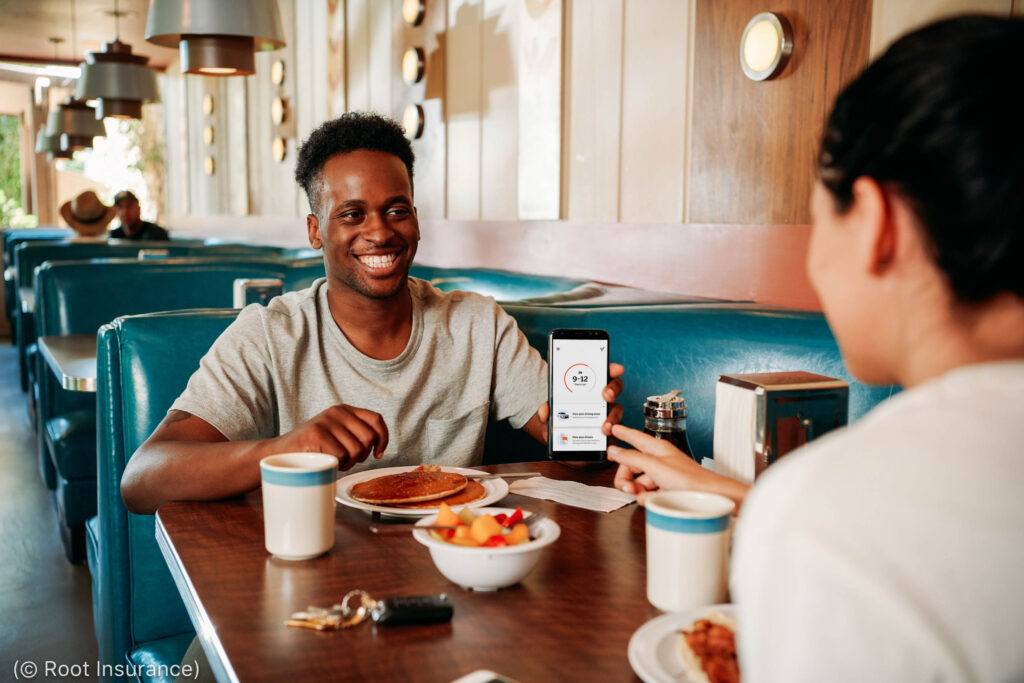 Man seated in restaurant booth showing smartphone screen to person across table (© Root Insurance)