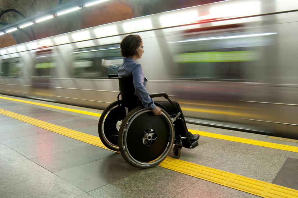 Person in a wheelchair on the train platform at a metro station.