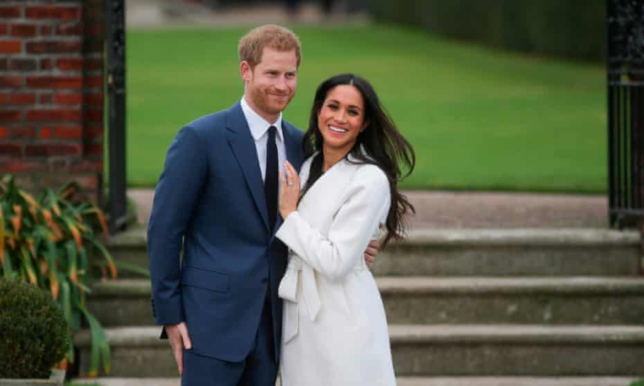 Harry and Meghan with their arms round each other outside in a garden at a photocall f