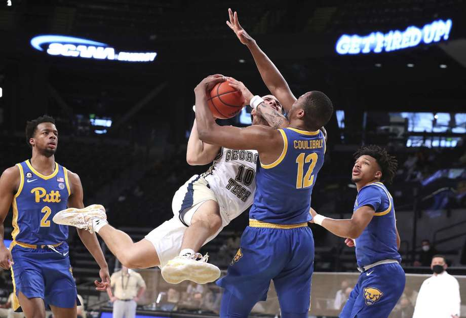 Georgia Tech guard Jose Alvarado is fouled by Pittsburgh forward Abdoul Karim Coulibaly (12) while driving to the basket during an NCAA college basketball game on Sunday, Feb. 14, 2021, in Atlanta. (Curtis Compton/Atlanta Journal-Constitution via AP) Photo: Curtis Compton, AP / Atlanta Journal-Constitution