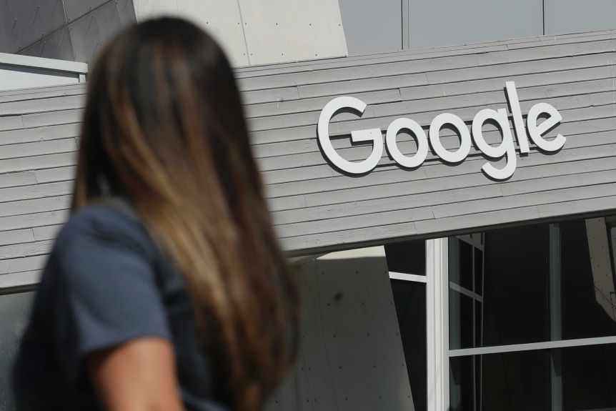 A woman walks below a Google sign on the company's campus