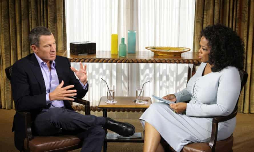 Armstrong in a dark suit and Winfrey in a light dress sitting at 45 degrees to each other in a room with a sideboard behind with two glasses of water on it