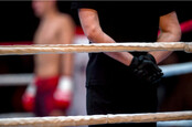 Boxing ring ropes and referee in black clothes