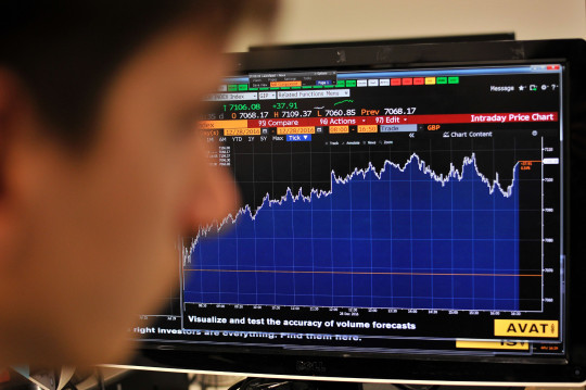 A journalist in London looks at the Intraday Price Chart showing London's FTSE 100 Index