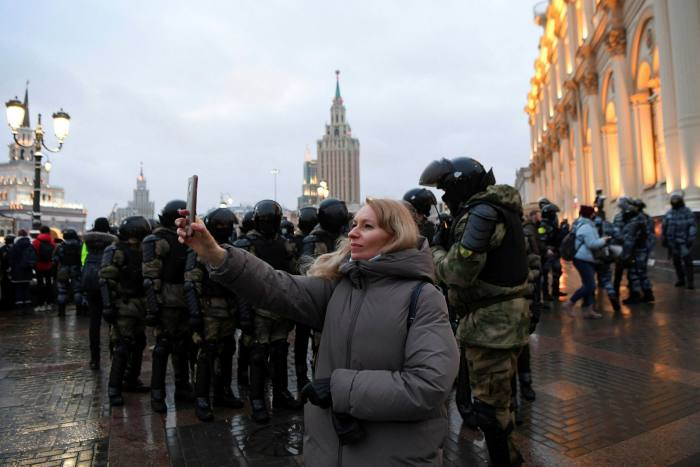 A demonstrator takes pictures with her smartphone during a January rally in support of Alexei Navalny in Moscow in front of law enforcement officers