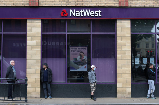 People maintain social distance while they queue outside a Natwest bank.