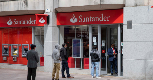People queuing outside a branch of Santander.
