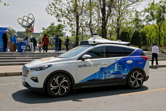 A Baidu Apollo Robotaxi passes its customer service counter setup at the Shougang Park in Beijing, Sunday, May 2, 2021. Chinese tech giant Baidu rolled out its paid driverless taxi service on Sunday, making it the first company that commercialized autonomous driving operations in China. (AP Photo/Andy Wong)