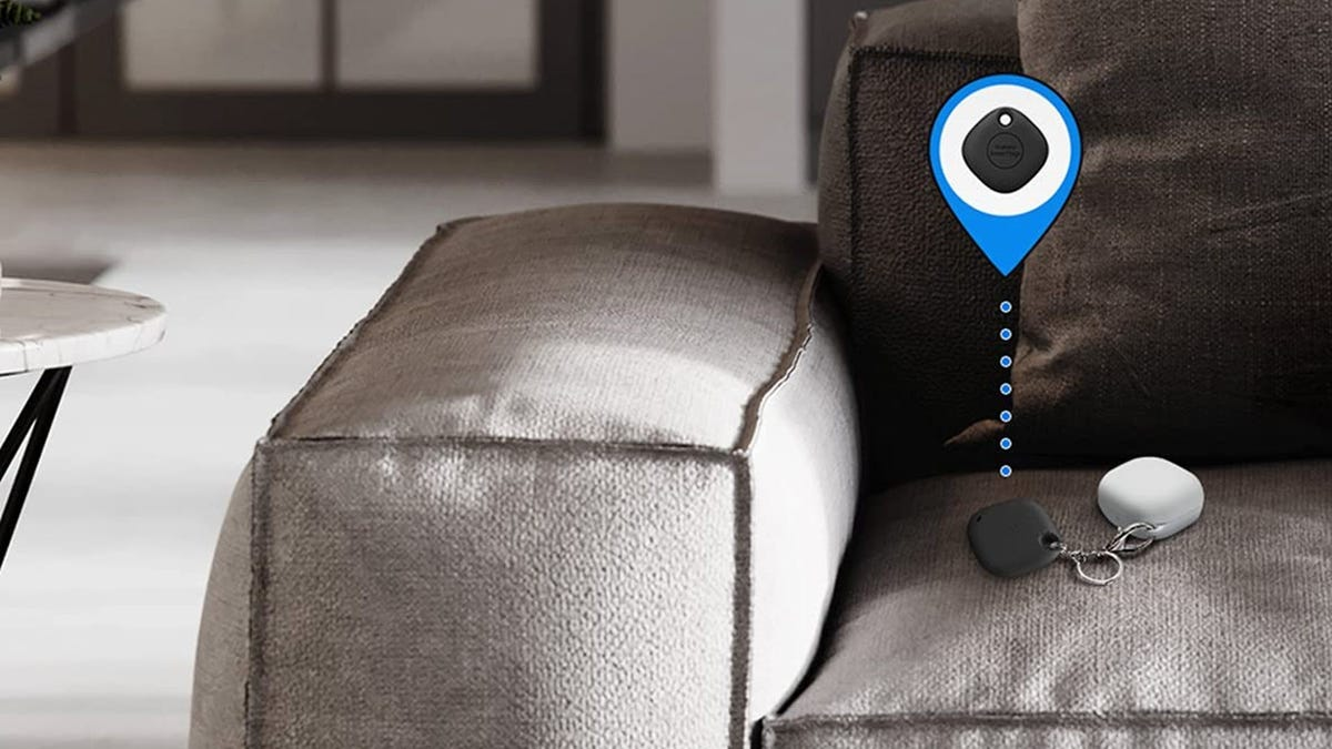 A SmartTag+ tracker, attached to some keys on a couch.