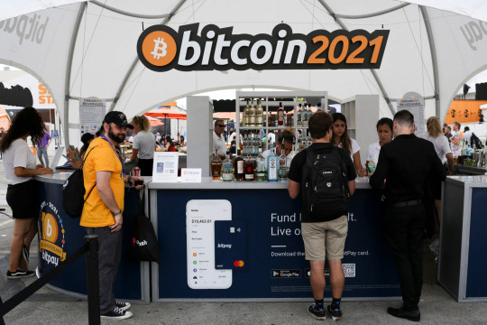 The logo of the crypto-currency conference Bitcoin 2021 Convention is seen as people buy drinks in a stand at the Mana Convention Center in Miami, Florida