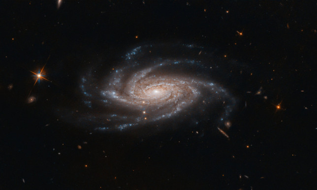 Undated handout photo issued by National Aeronautics and Space Administration (NASA) of the spiral galaxy NGC 2008 sitting centre stage, its ghostly spiral arms spreading out toward us