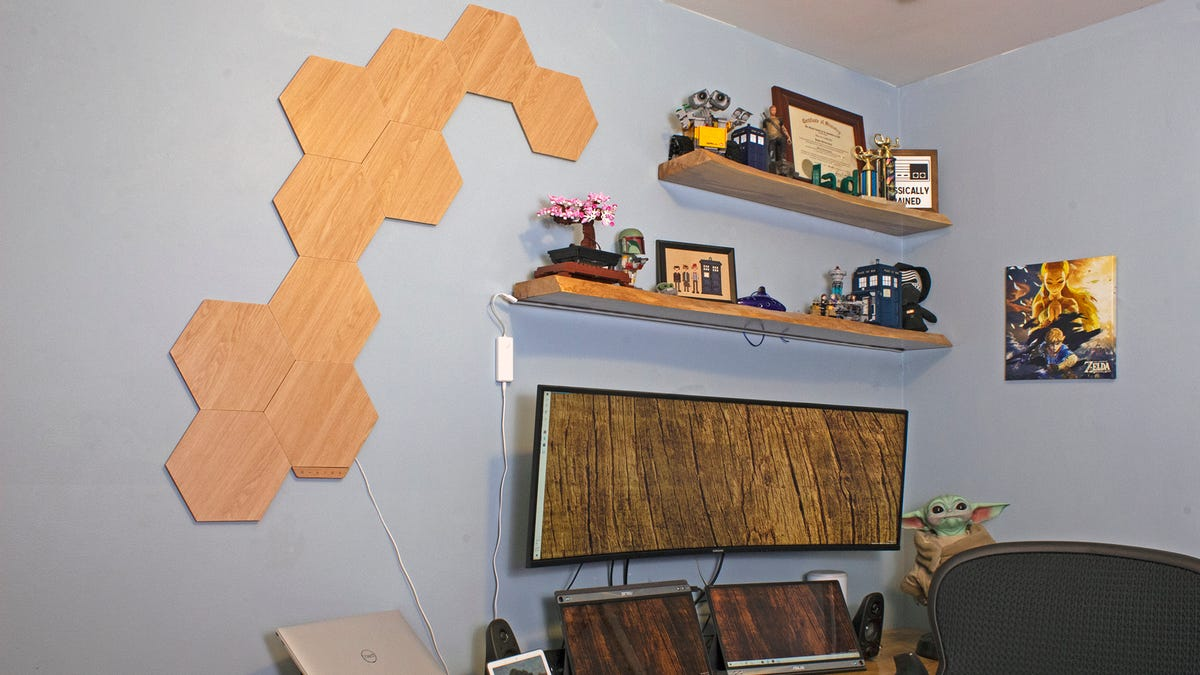 An office surrounded by wood furniture, with woodgrain hexagons on the wall.