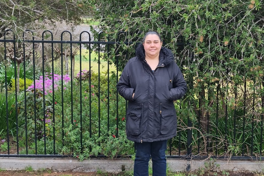 woman standing outside beside a hedge