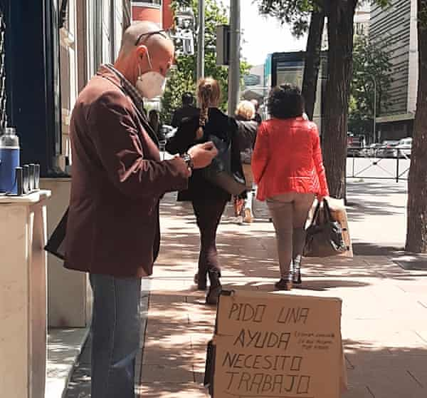 A man with a cardboard sign, looking for work