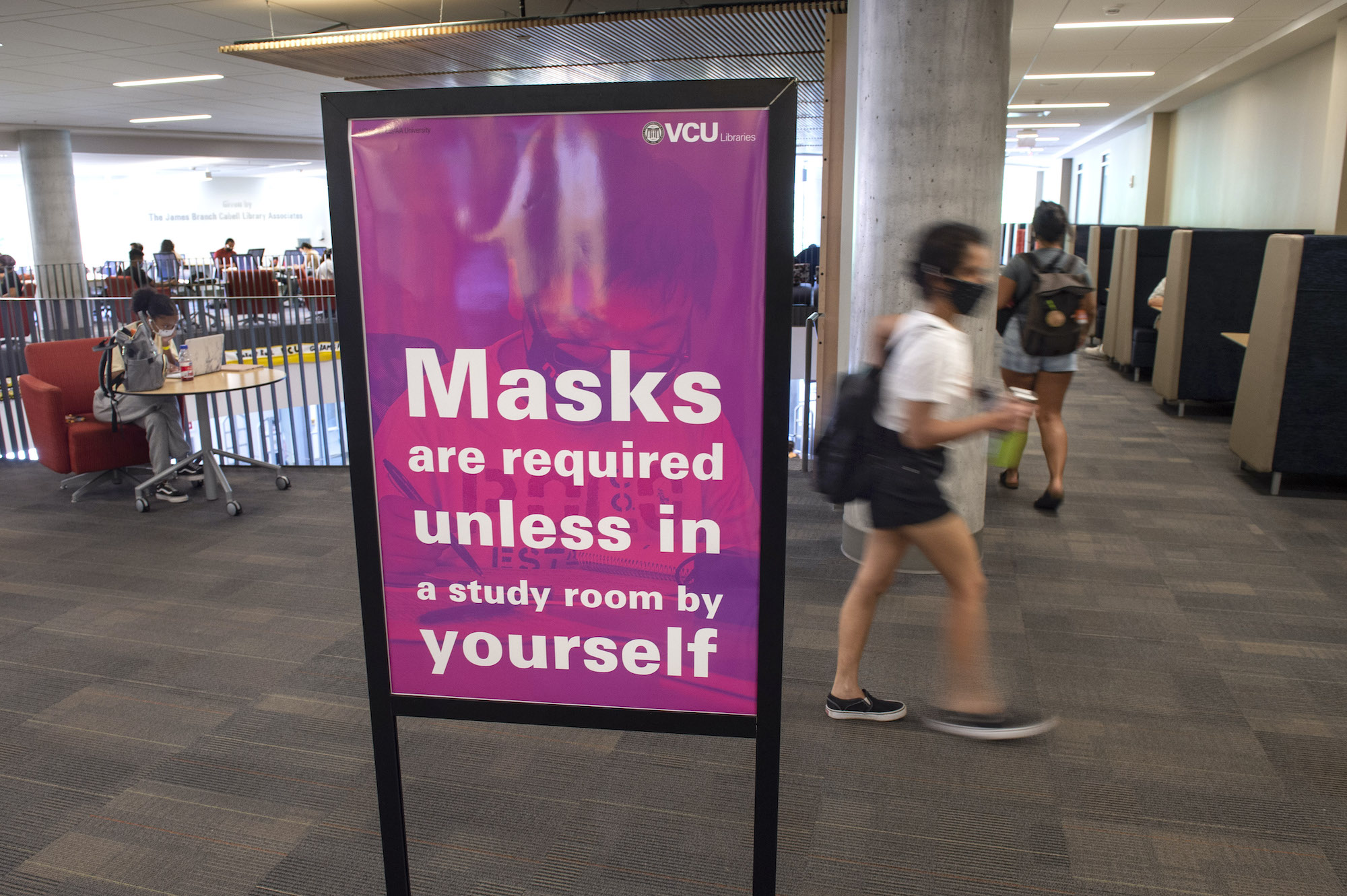 A sign outlining face mask requirements inside Cabell Library.