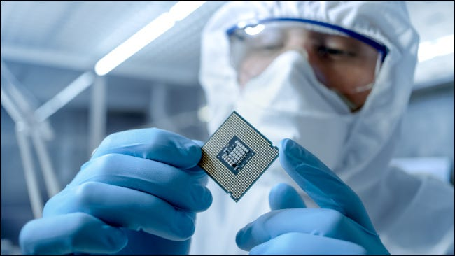 Man in sterile suit examining a microchip in a factory
