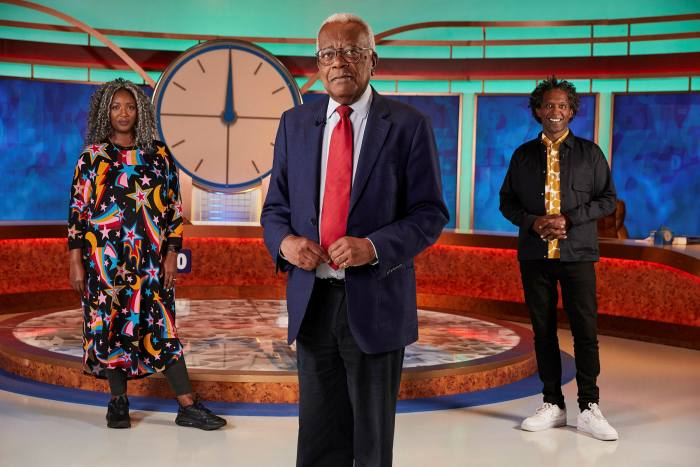Three people standing in a studio in front of contestants' desks