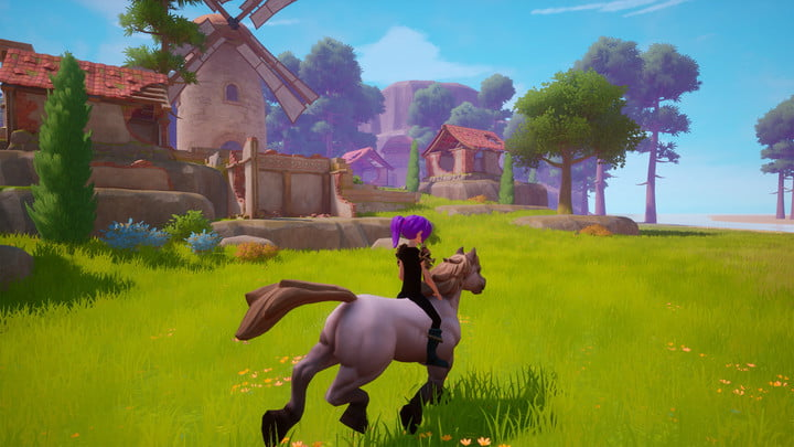 Riding a horse through the grass near a village.