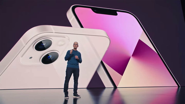 Tim Cook standing in front of an image of the pink iPhone 13.