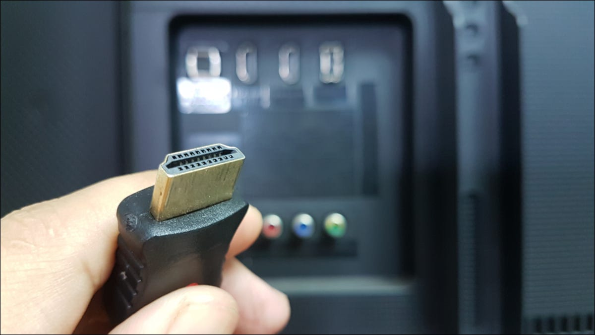 A hand holding an HDMI cable.