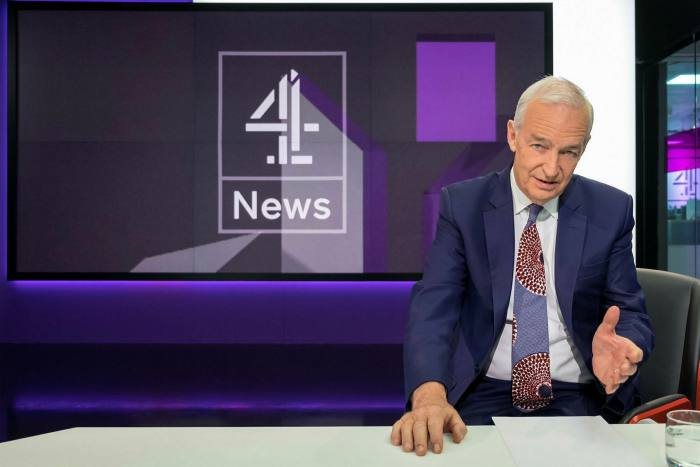 A man in a suit gesturing with one hand in front of a screen which says 4 News