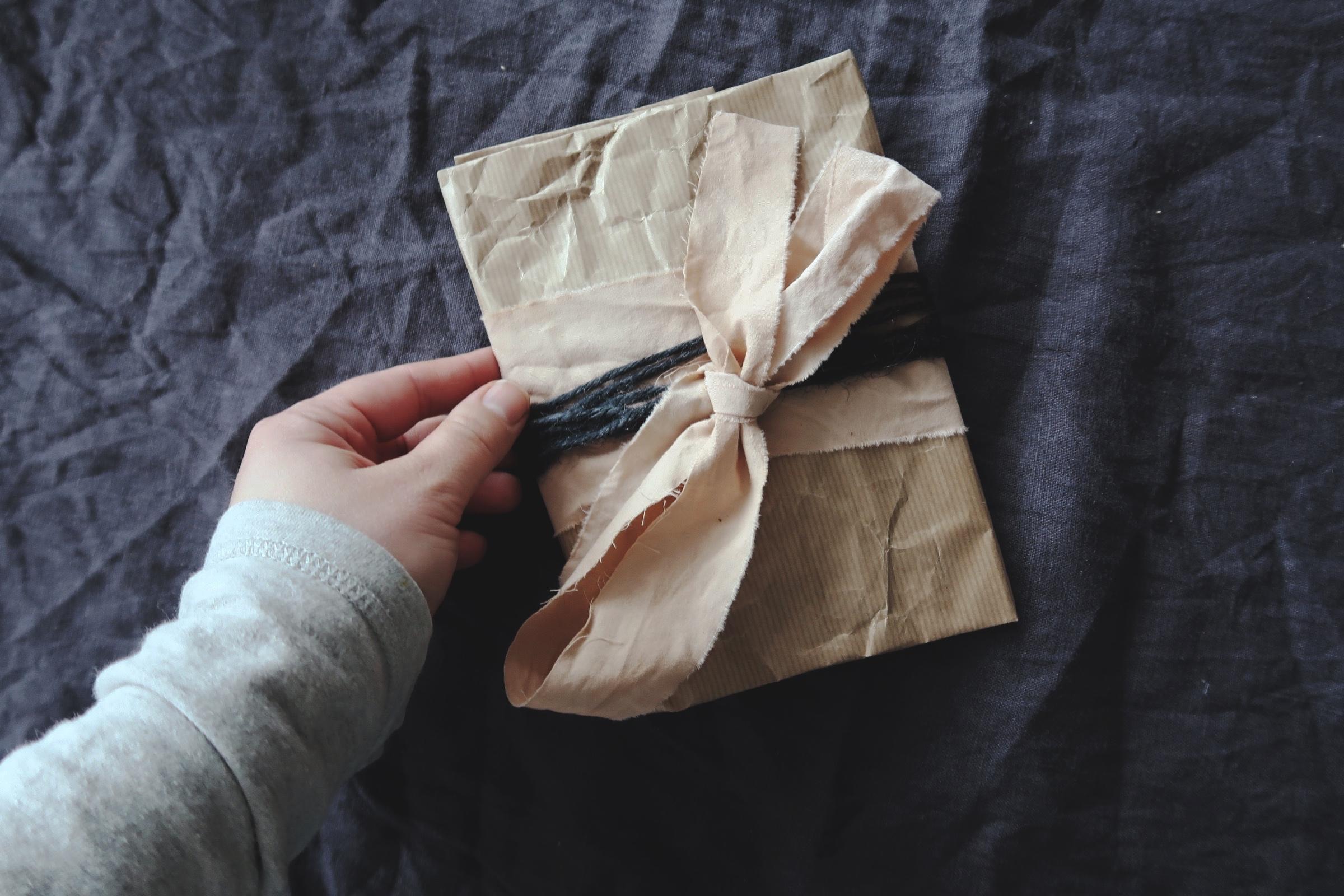 Paket inslaget med naturfärgat papper, växtfrägat band och svart snöre