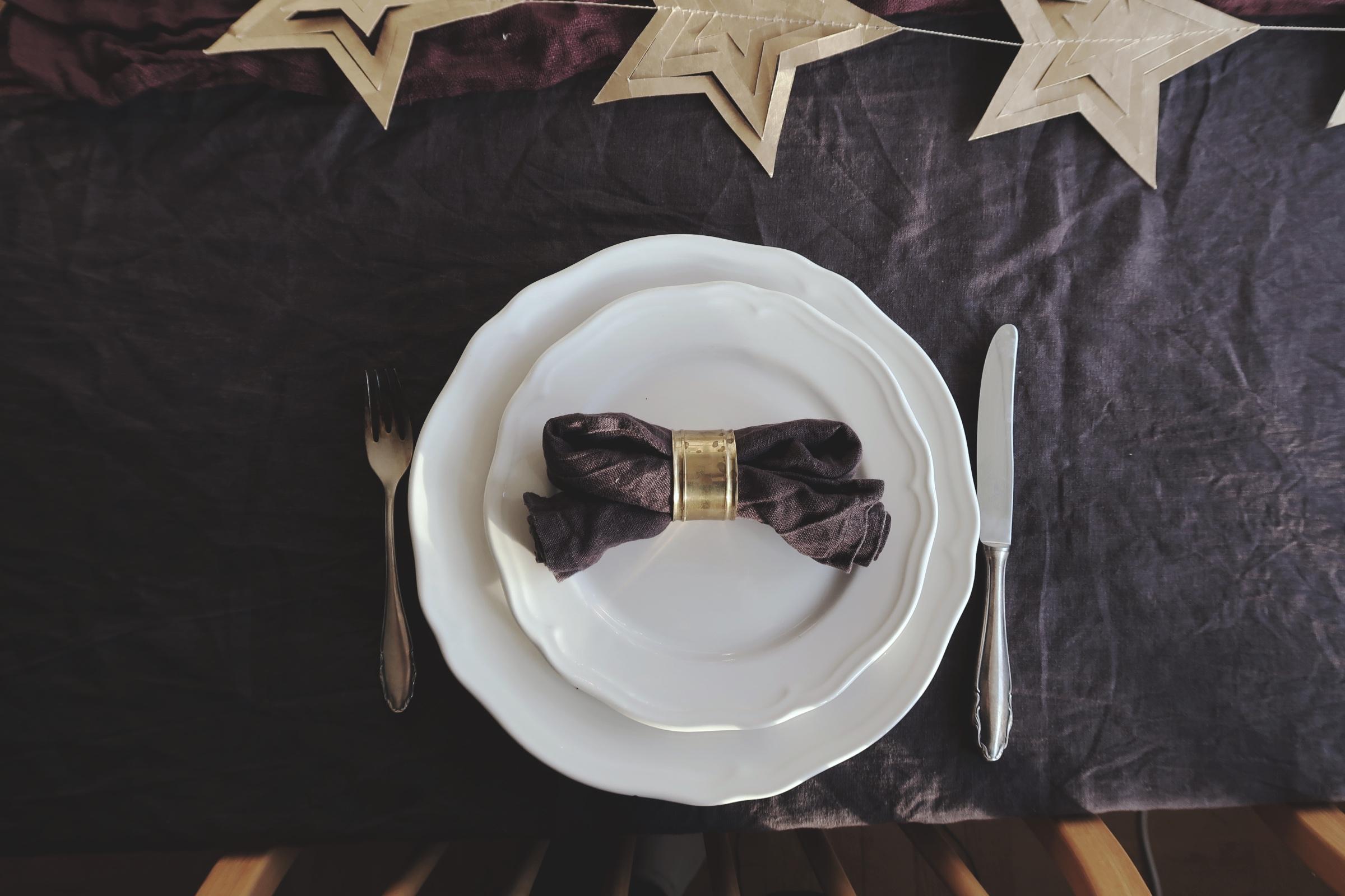 Mörkgrå linneservetter och servettring i mässing