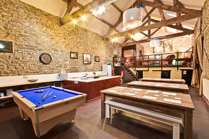 A view of the main area of the barn showing pool table and wooden eating tables/benches.
