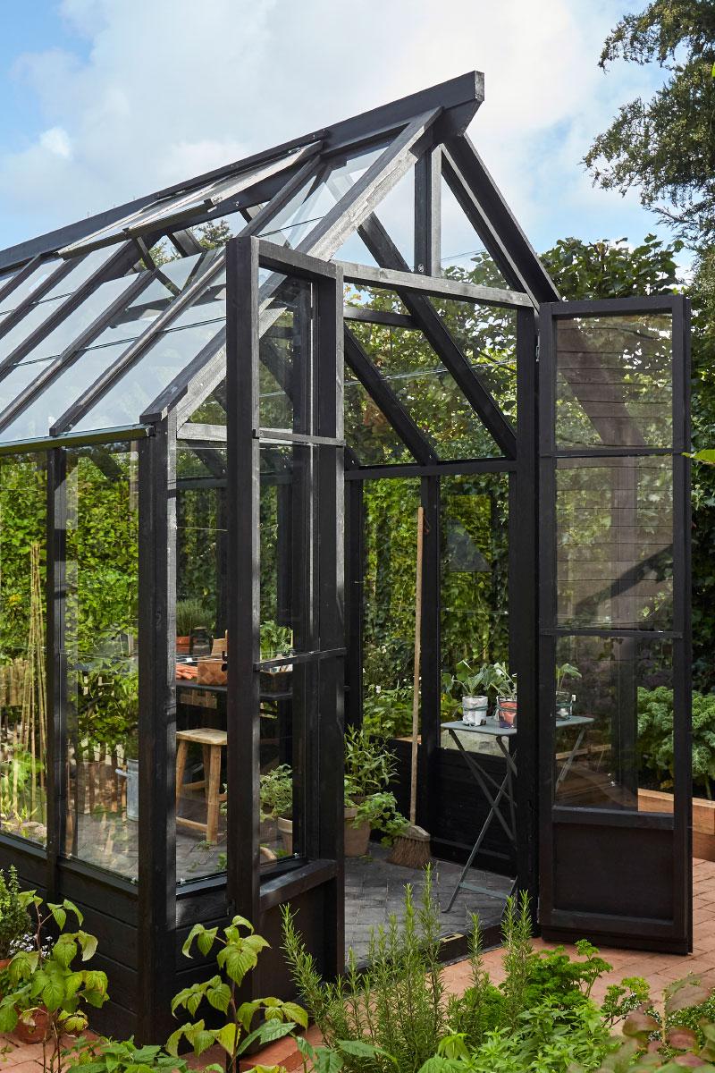 Sort trædrivhus fra siden med dørene åbne i en grøn have
