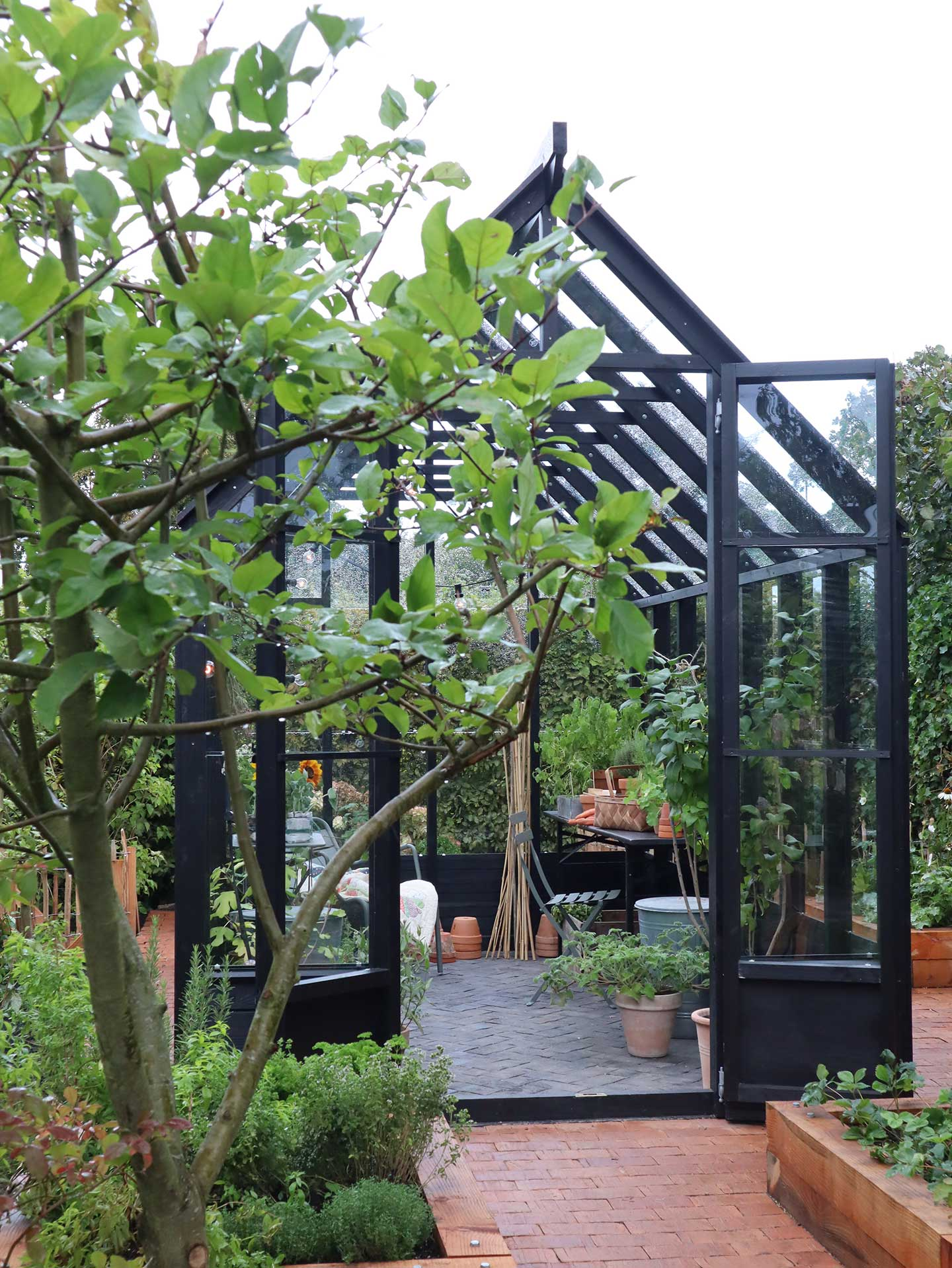 The Greenery på terrasse med åbne døre foran et træ