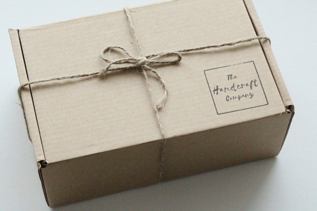 A rustic gift box with jute twine around it and a logo