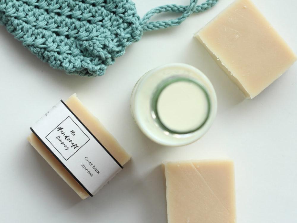 Goat milk handmade soap with washcloth and milk flat lay