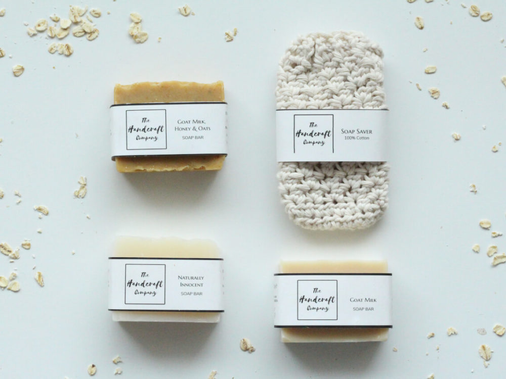 Unscented bars of soap with a white soap sack flat lay