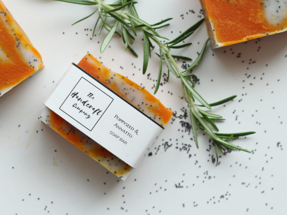 Poppy seeds and Annatto handmade natural soap with rosemary leaves flat lay