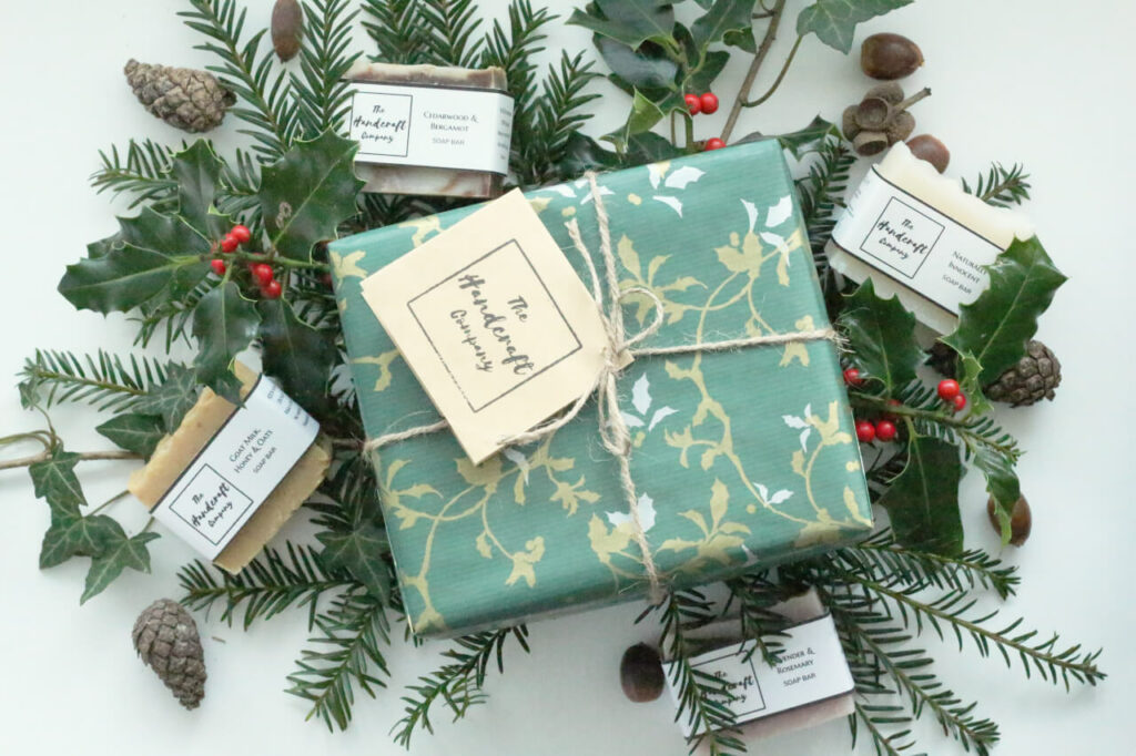 Wrapped gift on reef of holly and acorns and bars of soap