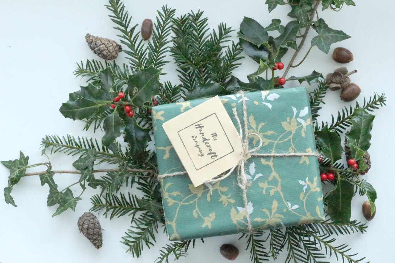 Wrapped gift on reef of acorns and holly