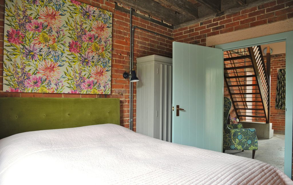 Double bedroom with exposed brick walls and quarry tile floor