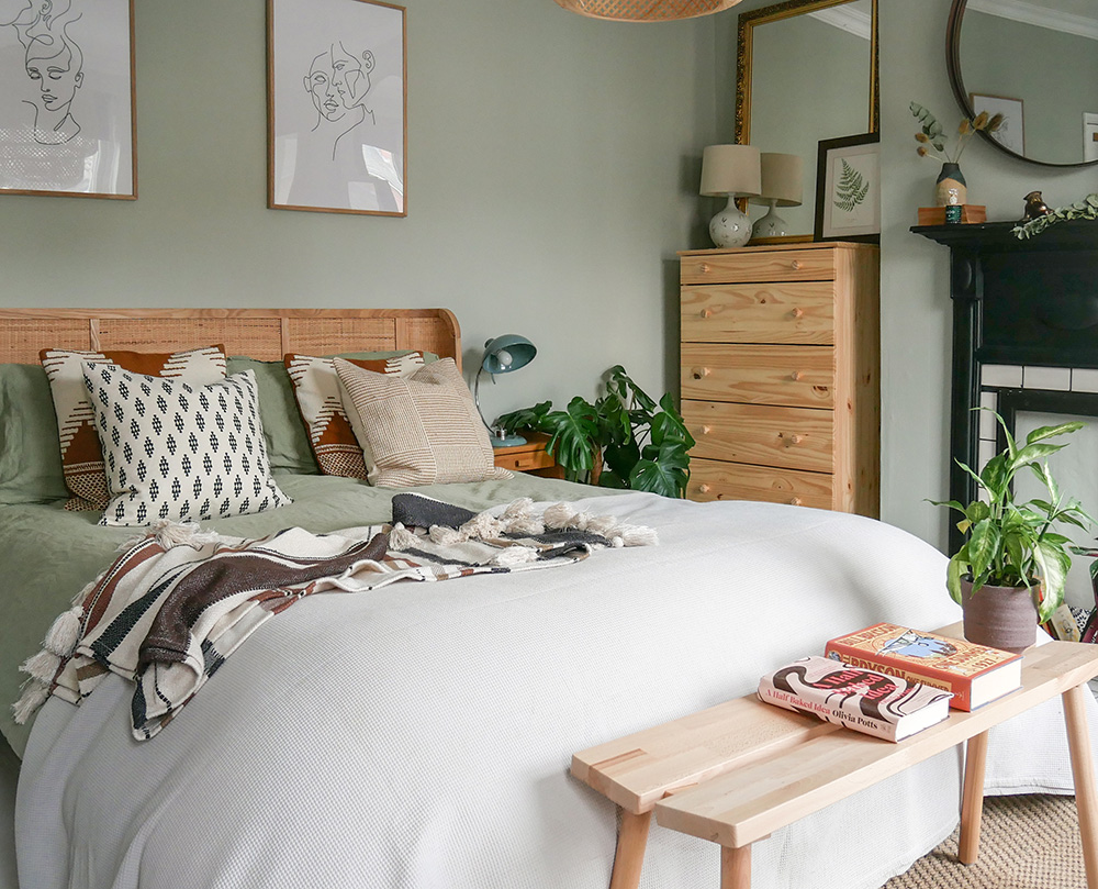 A boho bedroom with green walls and warm oak furniture